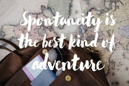 Photo pour Vue du dessus du sac en cuir avec passeport, billet, lunettes de soleil et carte avec spontanéité est le meilleur type d'illustration d'aventure - image libre de droit