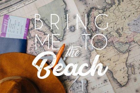 Foto de Vista superior del pasaporte con tarjeta de embarque, sombrero, auriculares y modelo de avión pequeño en el mapa con llevarme a la playa de letras - Imagen libre de derechos