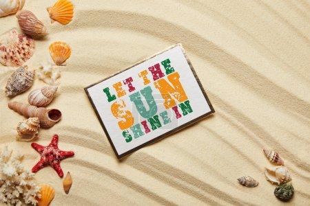 Photo pour Vue du dessus de la carte avec laissez le soleil briller dans le lettrage près des coquillages, étoiles de mer rouges et coraux sur la plage de sable - image libre de droit
