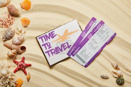 Photo pour Vue du haut de la carte avec le temps de voyager laissant près des billets d'avion et des coquillages sur la plage sablonneuse - image libre de droit
