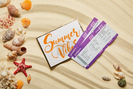 Photo for Top view of card with summer vibes letting near air tickets and seashells on sandy beach - Royalty Free Image