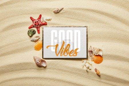 Photo pour Vue supérieure de l'affiche avec le lettrage de bonnes vibrations près des coquillages, des étoiles de mer et des coraux blancs sur la plage sablonneuse - image libre de droit