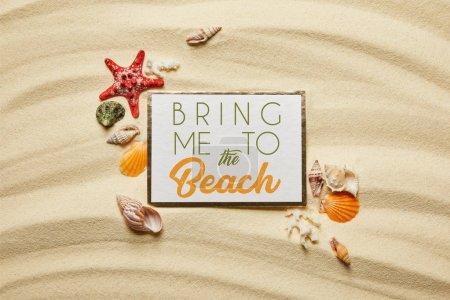 Photo pour Vue du dessus de la plaque avec m'amener à la plage lettrage près des coquillages, étoiles de mer et coraux blancs sur la plage de sable fin - image libre de droit