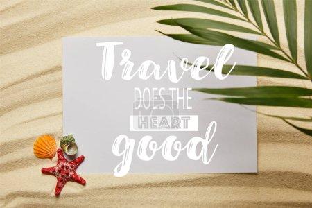 Photo pour Vue supérieure de la feuille verte de palmier près de l'affiche avec le voyage fait le bon coeur, étoiles de mer et coquillages sur la plage sablonneuse - image libre de droit