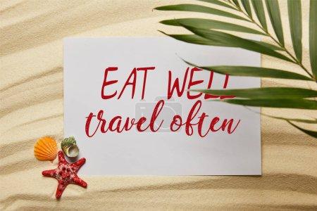 Photo pour Vue supérieure de la feuille verte de palmier près de l'affiche avec manger bien, voyage souvent lettrage, étoiles de mer et coquillages sur la plage sablonneuse - image libre de droit