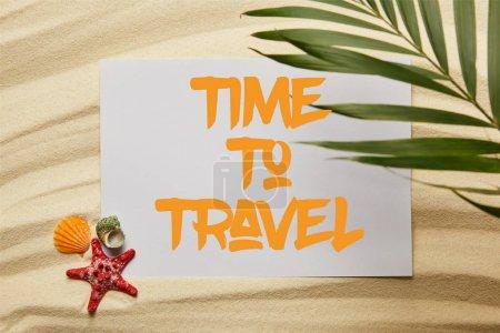 Photo pour Vue supérieure de la feuille verte de palmier près de l'affiche avec le temps de voyager lettrage, étoiles de mer et coquillages sur la plage sablonneuse - image libre de droit