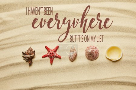 Foto de Plana sencina de conchas marinas y estrellas de mar rojas en la playa de arena en verano con no he estado en todas partes, pero está en mi lista dejando - Imagen libre de derechos