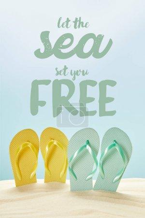 Photo pour Tongs jaunes et bleues d'été dans le sable doré isolé sur le bleu avec laissez la mer vous mettre le lettrage libre - image libre de droit
