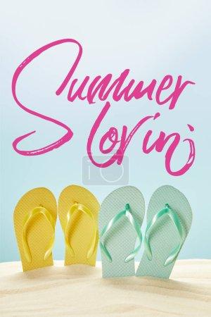 Photo pour Tongs jaunes et bleues d'été dans le sable doré d'isolement sur le bleu avec le lettrage d'amour d'été - image libre de droit