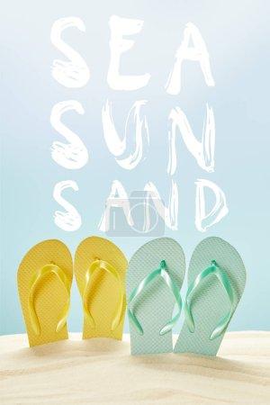Photo pour Tongs jaunes et bleues d'été en sable doré isolé sur bleu avec lettrage mer, soleil et sable - image libre de droit