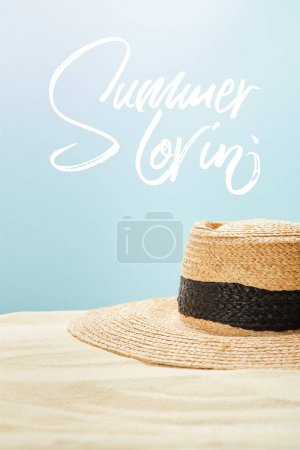 Photo for Selective focus of straw hat on golden sand in summertime isolated on blue with summer lovin lettering - Royalty Free Image