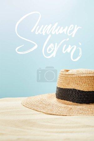 Photo pour Foyer sélectif du chapeau de paille sur le sable d'or en été isolé sur le bleu avec le lettrage de lovin d'été - image libre de droit
