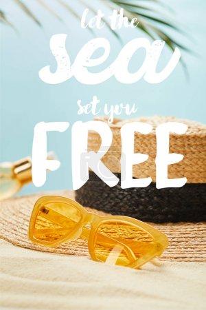 Photo pour Lunettes de soleil près du chapeau de paille et de la bouteille avec de l'huile de bronzage sur la plage de sable d'isolement sur le bleu avec laissez la mer vous mettre lettrage libre - image libre de droit