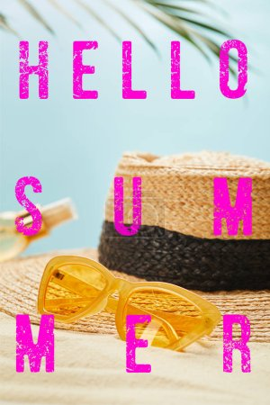 Photo for Sunglasses near straw hat and bottle with suntan oil on sandy beach isolated on blue with hello summer illustration - Royalty Free Image