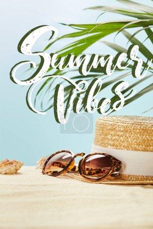 Foto de Gafas de sol cerca de sombrero de paja y conchas marinas en verano aislado en azul con vibraciones de verano ilustración - Imagen libre de derechos