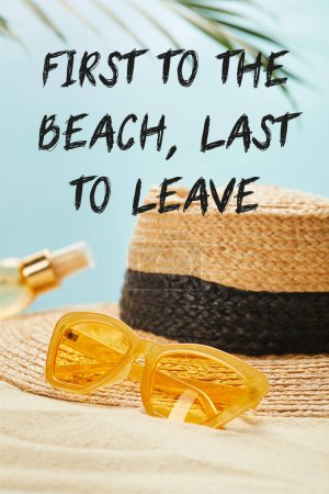 Photo for Sunglasses near straw hat and bottle with suntan oil on sandy beach isolated on blue with first to the beach, last to leave illustration - Royalty Free Image