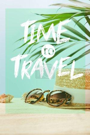 Foto de Gafas de sol cerca de sombrero de paja y conchas marinas en verano en el fondo azul con tiempo para viajar letras - Imagen libre de derechos