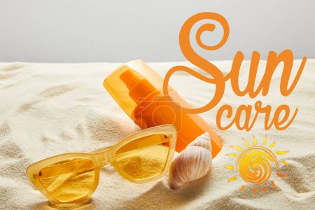 Photo for Yellow stylish sunglasses and sunscreen in orange bottle on sand with seashell on grey background with sun care lettering - Royalty Free Image