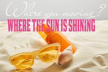 Photo pour Lunettes de soleil élégantes jaunes et crème solaire en bouteille orange sur sable avec coquillage sur fond gris avec où vous déplacer question et où le soleil brille réponse - image libre de droit