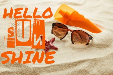 brown stylish sunglasses and sunscreen in orange bottle on sand with hello sunshine lettering
