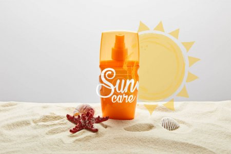 Photo for Sunscreen in orange bottle on sand with starfish on grey background with sun care lettering - Royalty Free Image
