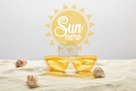 yellow stylish sunglasses on sand with seashell on grey background with sun care lettering