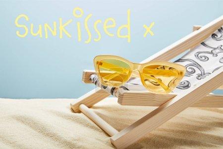 Photo pour Lunettes de soleil élégantes jaunes sur la chaise de plate-forme sur le sable sur le fond bleu avec le lettrage ensoleillé - image libre de droit