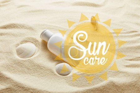 Foto de Protector solar en botella blanca sobre arena con conchas marinas y letras de cuidado solar - Imagen libre de derechos