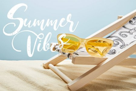 Photo for Yellow stylish sunglasses on deck chair on sand and blue background with summer vibes lettering - Royalty Free Image