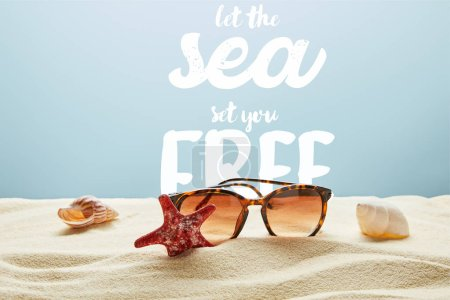 Photo for Brown stylish sunglasses on sand with seashells and starfish on blue background with let the sea set you free lettering - Royalty Free Image