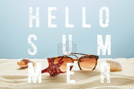 Photo pour Lunettes de soleil élégantes brunes sur le sable avec des coquillages et des étoiles de mer sur le fond bleu avec le lettrage d'été de bonjour - image libre de droit
