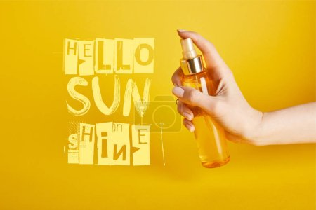 Photo for Cropped view of woman holding bottle with sunscreen spray on yellow background with hello sunshine lettering - Royalty Free Image