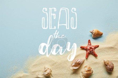 Photo pour Vue supérieure du sable avec des coquillages et des étoiles de mer sur le fond bleu avec des mers le lettrage de jour - image libre de droit