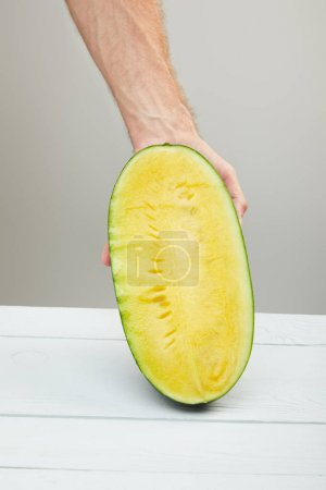 Photo for Cropped view of man holding ripe yellow watermelon half on wooden table isolated on grey - Royalty Free Image