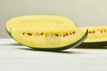ripe yellow tasty watermelon with seeds on white wooden table isolated on grey