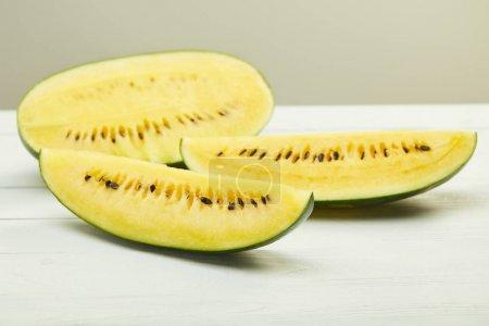 Photo pour Melon d'eau jaune savoureux avec des graines sur table en bois blanc isolé sur gris - image libre de droit