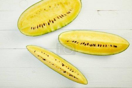 Photo pour Vue de dessus de pastèque jaune mûre savoureuse avec des graines sur table en bois blanc - image libre de droit