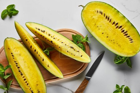 Photo for Top view of cut delicious exotic yellow watermelon with seeds on wooden chopping board with knife and mint on marble surface - Royalty Free Image