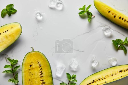 Photo for Top view of cut delicious exotic yellow watermelon with seeds on marble surface with mint, ice and copy space - Royalty Free Image