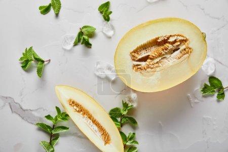 Photo pour Vue de dessus du délicieux melon coupé avec des graines sur la surface du marbre avec menthe et glace - image libre de droit