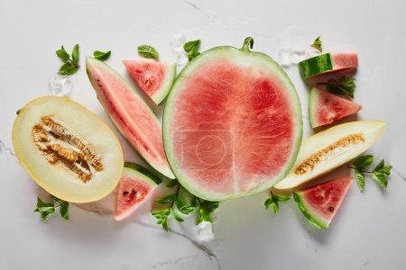 Photo pour Vue de dessus de la coupe délicieuse pastèque exotique rouge avec melon sur la surface de marbre avec glace et menthe - image libre de droit