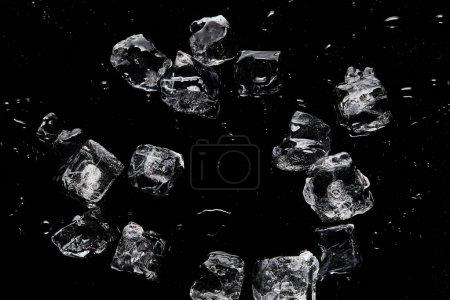 Photo pour Vue du haut de la fonte des glaçons rafraîchissants transparents isolés sur le noir - image libre de droit