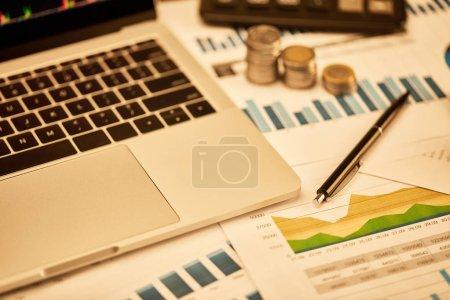 Photo pour Ordinateur portatif, pièces de monnaie, papiers et stylo sur la table dans le bureau - image libre de droit