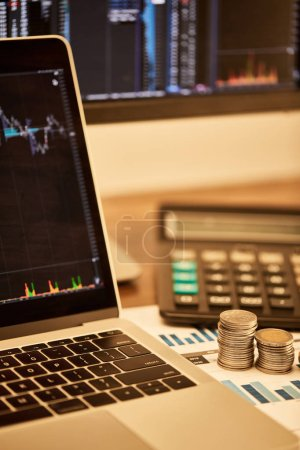 selective focus of laptop, coins, papers and calculator on table