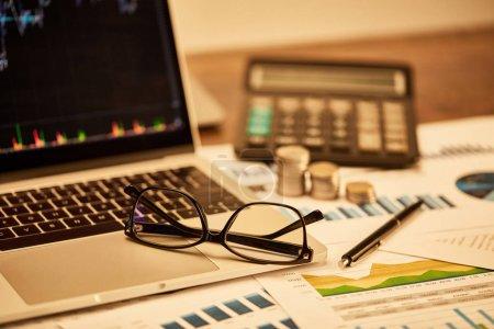 Photo pour Selective focus of laptop, coins, papers, glasses, pen and calculator on table - image libre de droit