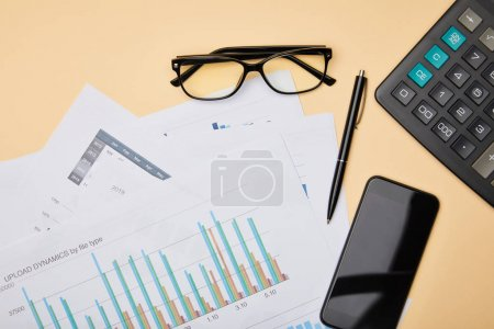 top view of papers, pen, calculator, smartphone and glasses on table