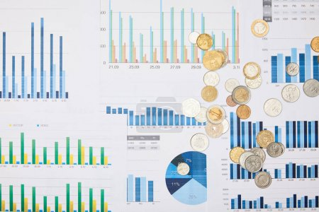 Photo for Top view of papers with graphs and coins on table - Royalty Free Image
