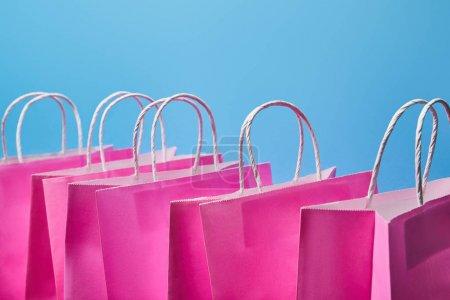 Photo pour Quelques sacs à provisions en papier rose sur fond bleu - image libre de droit