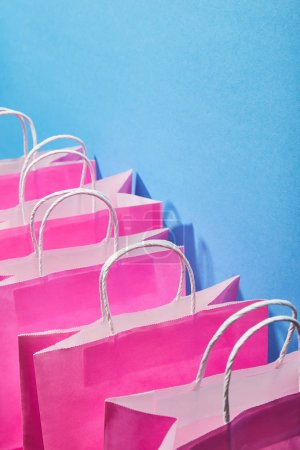 Photo for Pink shopping bags with white handles on blue background - Royalty Free Image