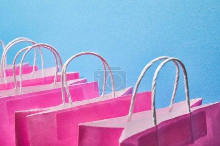 sacs en papier rose avec poignées blanches sur fond bleu